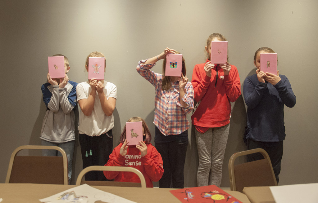 """ASAE students in grades 4–6 show off artwork they made, inspired by Sylvia Taylor's """"Pink Cloud"""" installation."""