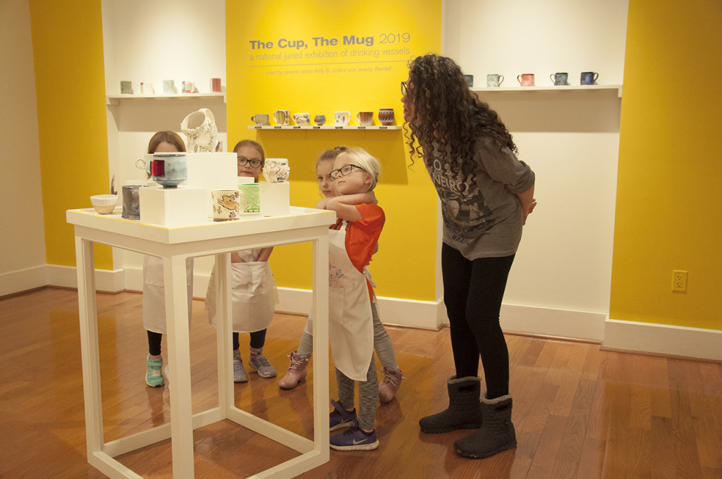 """ASAE students in grades 1–3 discuss ceramics as they look at this year's """"The Cup, The Mug"""" exhibition"""