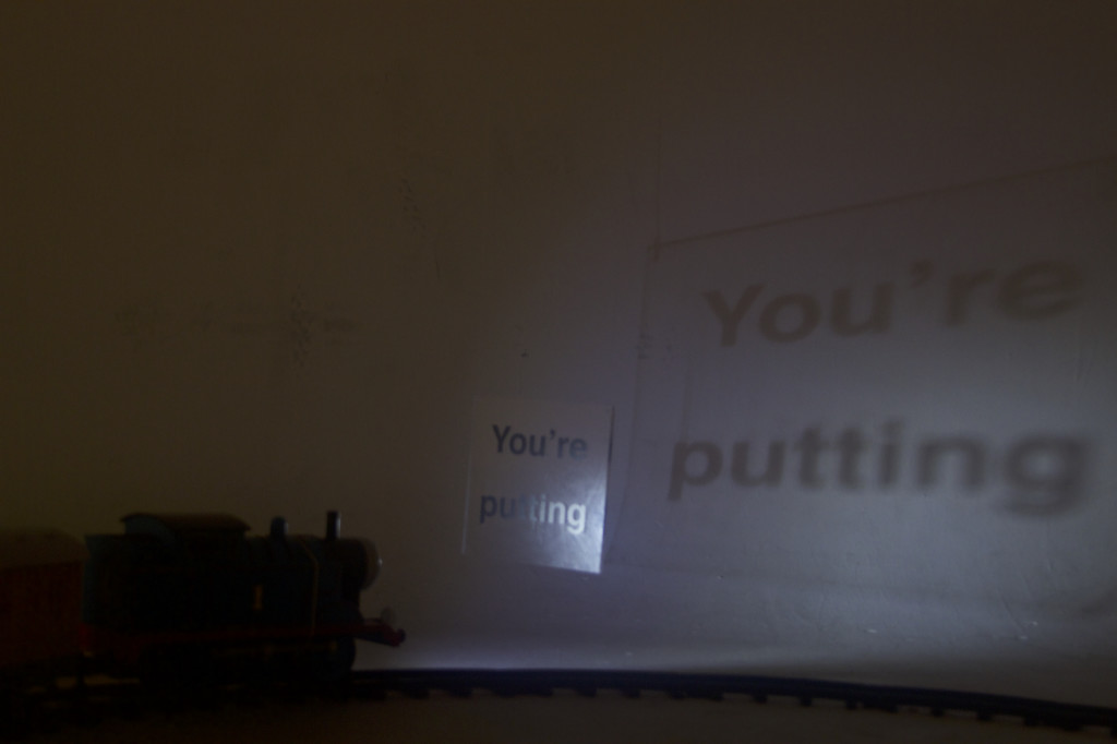 """""""Trauma train"""" is an installation consisting of a Thomas the Tank Engine toy train set, to which is attached a flashlight that projects text onto the walls as the train goes around the track and shines through pieces of clear acrylic affixed with black vinyl lettering hung from the ceiling."""