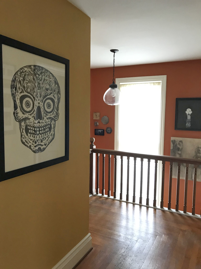 A view down our upstairs hallway, looking at the stairwell. The skull print on the left, by Bill Fick, was acquired from Rochester Contemporary during the Outlaw Printmakers Show in 2014.