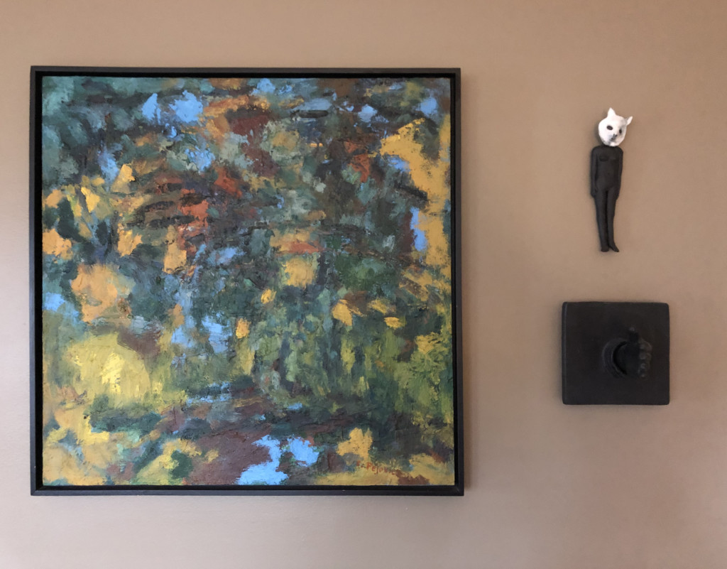 A painting by Lanna Pejovic is joined by two ceramic sculptures, the small masked figure at the top is by Carrianne Hendrickson and the handshake tile is by Bill Stewart.