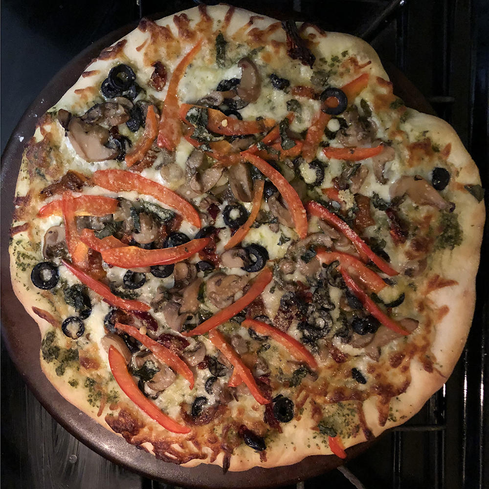 Homemade crust with homemade pesto, red peppers, black olives, mushrooms, and sun dried tomatoes