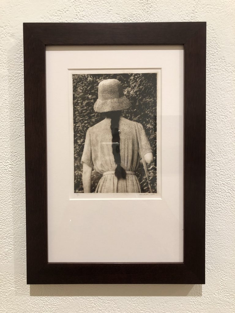 photogravure print of a woman in a hat from behind